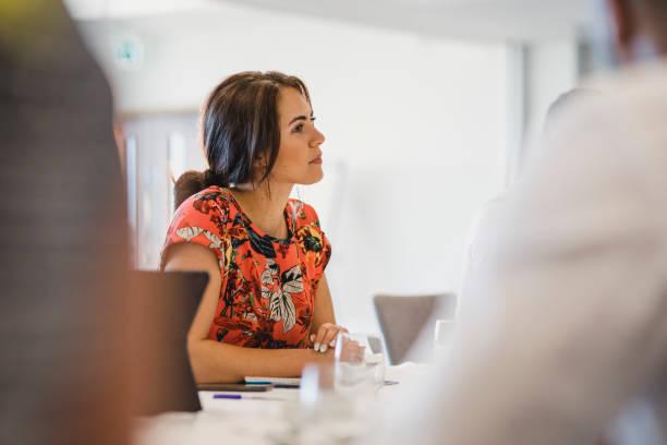 atrakcyjna młoda kobieta siedząca przy stole na spotkaniu biznesowym - selektywna głębia ostrości zdjęcia i obrazy z banku zdjęć