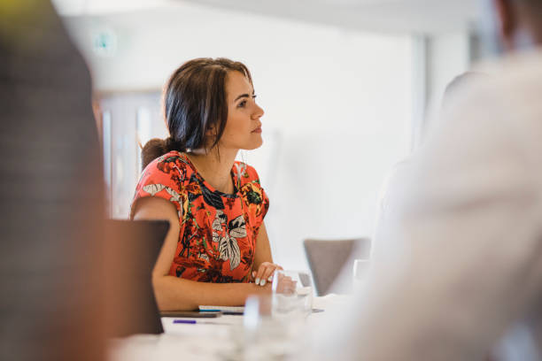 Attractive young woman sitting at table in business meeting