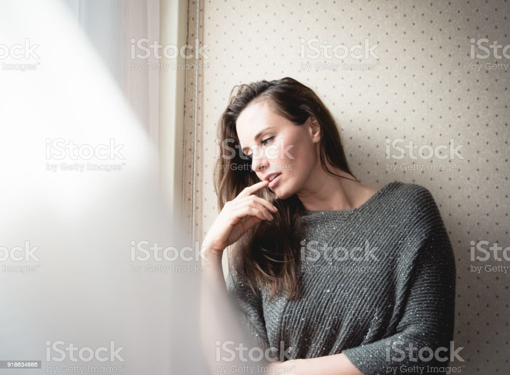 Attractive young woman sitting daydreaming stock photo