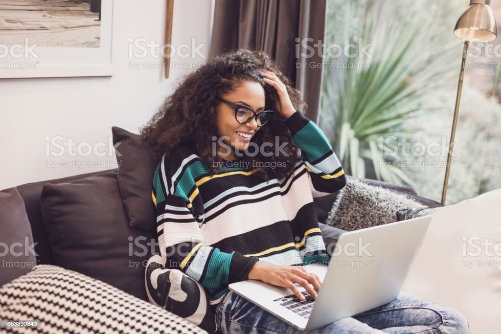 Attraktive junge Frau sitzt auf dem Sofa mit ihrem laptop – Foto