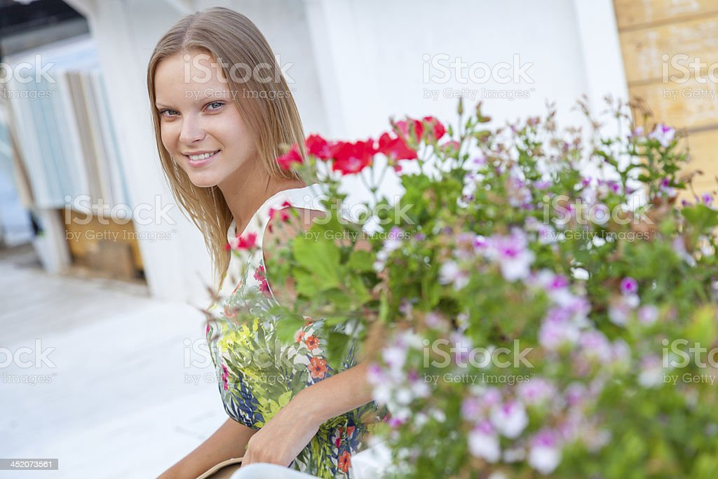 Attractive young woman sitting on bench surrounded by flowers royalty-free stock photo