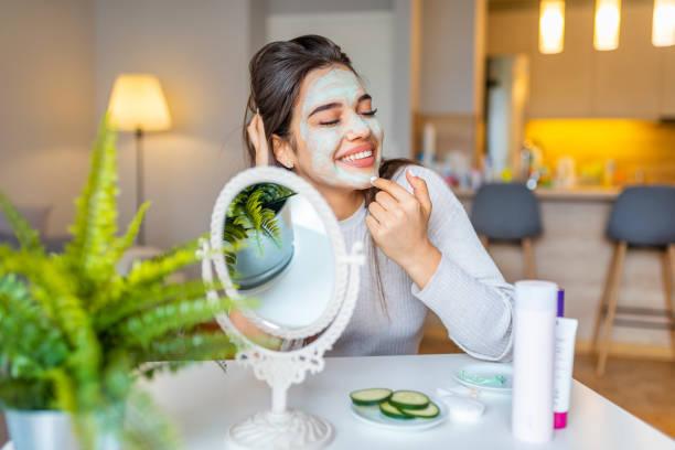 aantrekkelijke jonge vrouw zittend met een gezichtsmasker op haar huid - mirror mask stockfoto's en -beelden