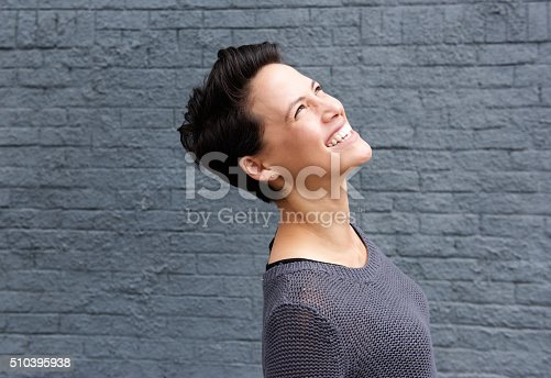 istock Attractive young woman smiling and looking up 510395938