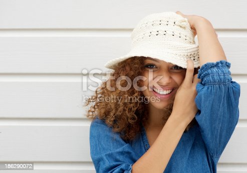 186534921 istock photo Attractive young woman smiling and wearing hat on white background 186290072