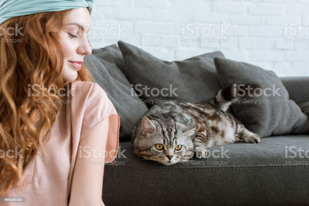 attractive young woman smiling at adorable tabby cat at home stock photo