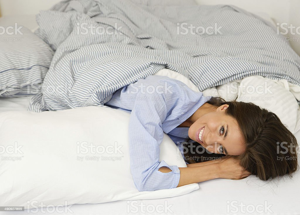 Attractive young woman smiling in bed stock photo