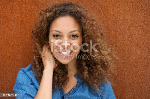 186534921 istock photo Attractive young woman smiling with hand in hair 462528237