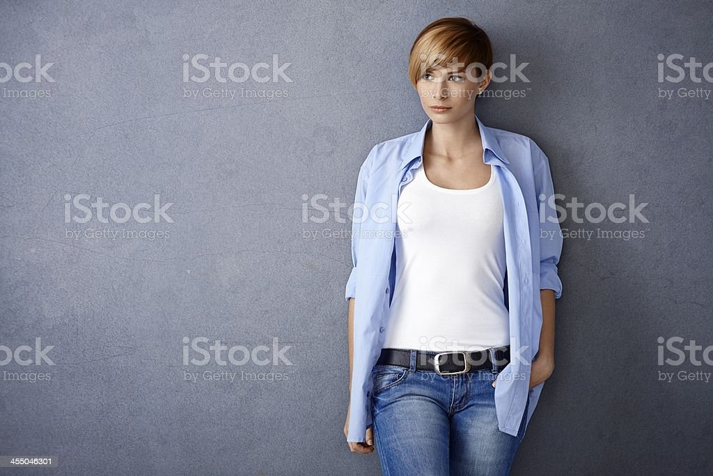 Attractive young woman standing by wall stock photo