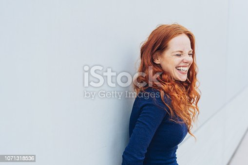 Attractive young woman standing giggling or laughing at something she finds very funny while leaning against a white exterior wall with copy space