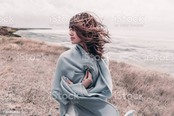 Attractive young woman standing on a windy cold beach wrapped in warm picture id1164869534?b=1&k=6&m=1164869534&s=612x612&h=h0dxcf54c2svkop40vh fv28yp s5jkumkefeq9ydzo=