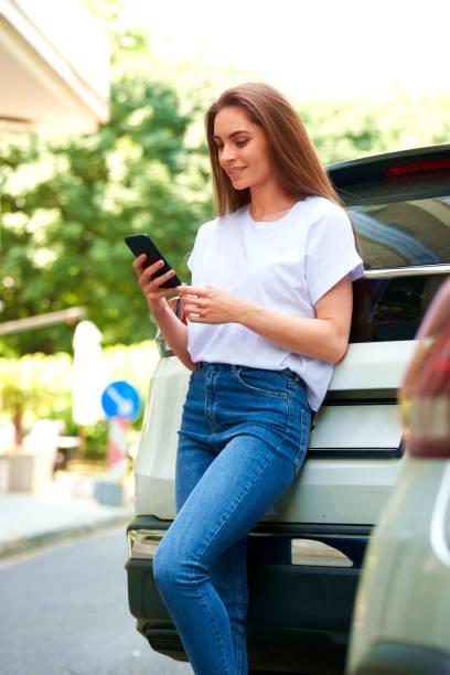 Attraktive junge Frau auf der Straße stehen und SMS – Foto