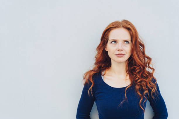 Attractive young woman standing pondering Attractive young woman standing pondering a problem looking up with a contemplative expression against a white exterior wall with copy space redhead stock pictures, royalty-free photos & images