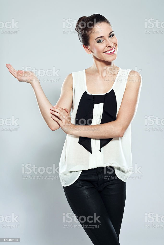 Attractive young woman, Studio Portrait Portrait of attractive young woman pointing at copy space and smiling at camera. Studio shot on a grey background. 20-24 Years Stock Photo