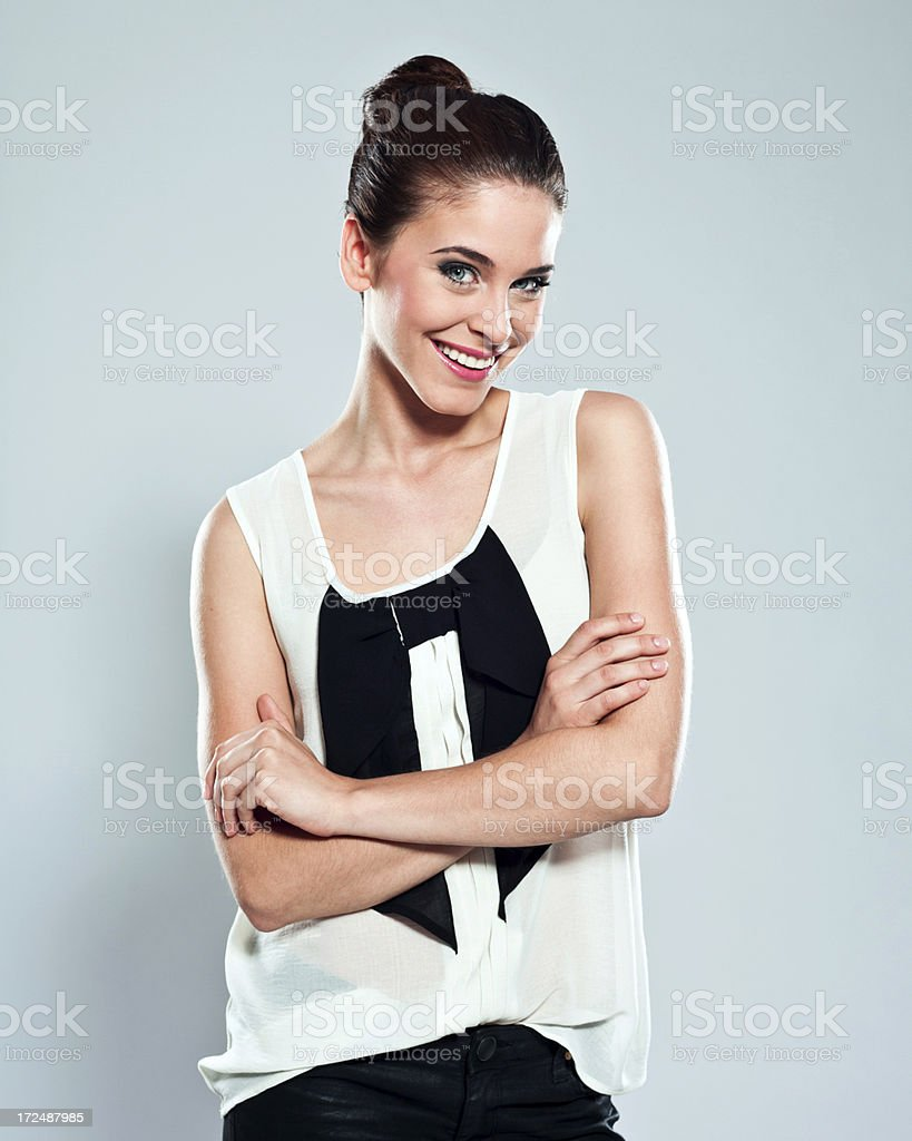 Attractive young woman, Studio Portrait Portrait of attractive young woman smiling at the camera. Studio shot on a grey background. 20-24 Years Stock Photo