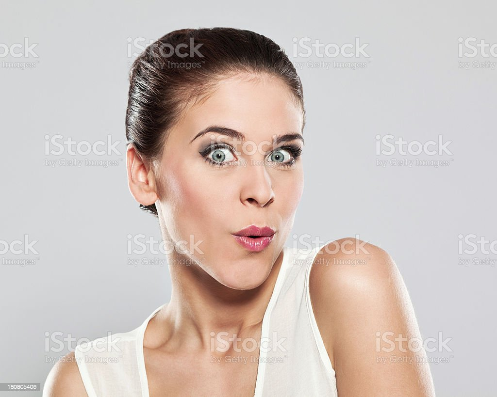 Attractive young woman, Studio Portrait Portrait of surprised young woman whistling at the camera. Studio shot on a grey background. 20-24 Years Stock Photo