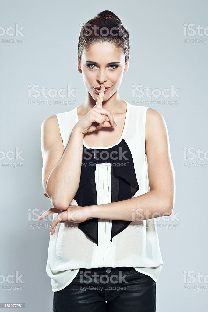 Attractive young woman, Studio Portrait Portrait of attractive young woman looking at camera with finger on lips. Studio shot. 20-24 Years Stock Photo