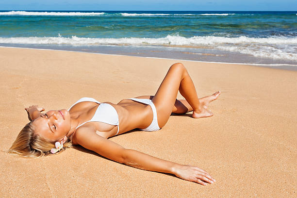 attractive young woman sunbathing in white bikini - busty women in bikinis stock pictures, royalty-free photos & images