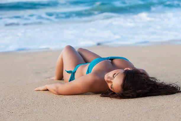 attractive young woman sunbathing on hawaiian beach - hawaiian ethnicity stock photos and pictures