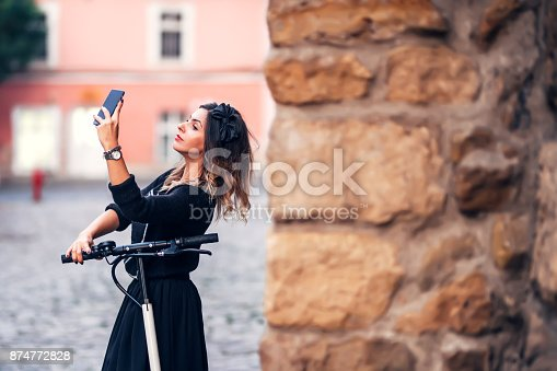 874772840istockphoto Attractive young woman taking selfie on city streets. Portrait of young woman making faces at camera 874772828