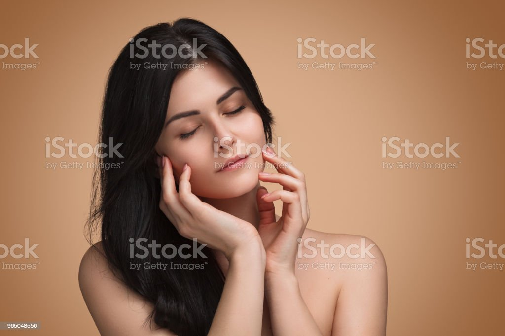 Attractive young woman touching face with eyes closed royalty-free stock photo