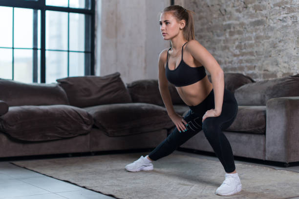 Attractive young woman training indoors doing side lunges working out legs, hips and buttocks stock photo