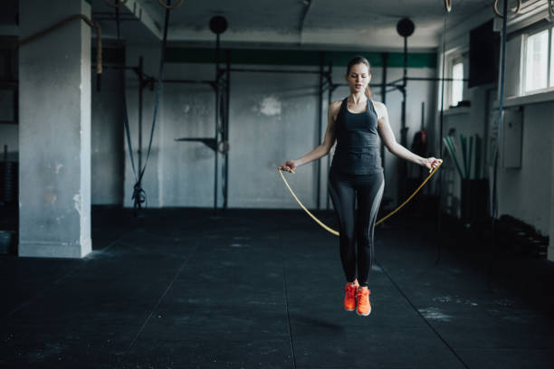Attractive young woman uses jumping rope to train stock photo