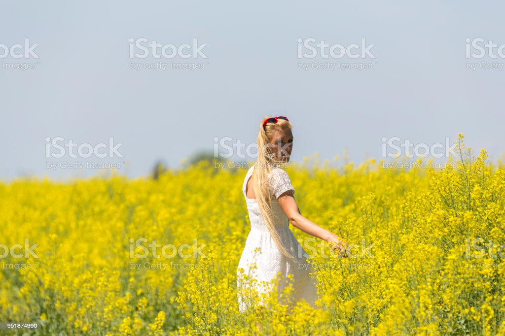 Attractive young woman walking though rapeseed fields looking at camera stock photo