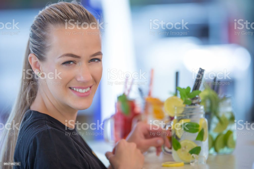 Attractive young woman with a beautiful smile while working in a bar preparing lemonades royalty-free stock photo