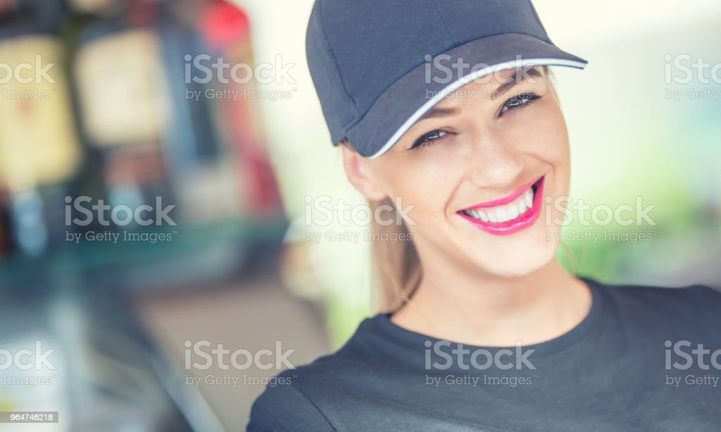 Attractive young woman with a beautiful smile while working in a bar royalty-free stock photo