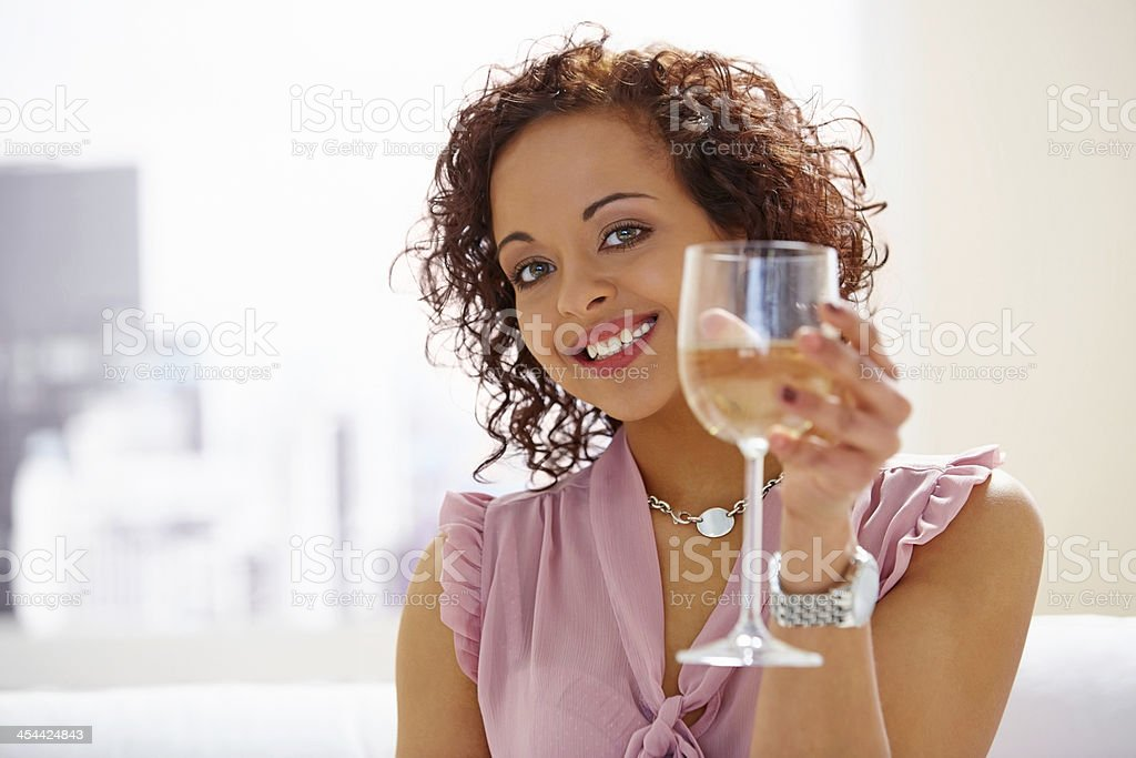 Attractive young woman with a glass of wine smiling royalty-free stock photo