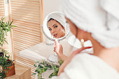 Attractive young woman with a white towel on her head dressed in bathrobe looks at herself in the mirror in stylish bathroom after morning shower. Beauty concept.