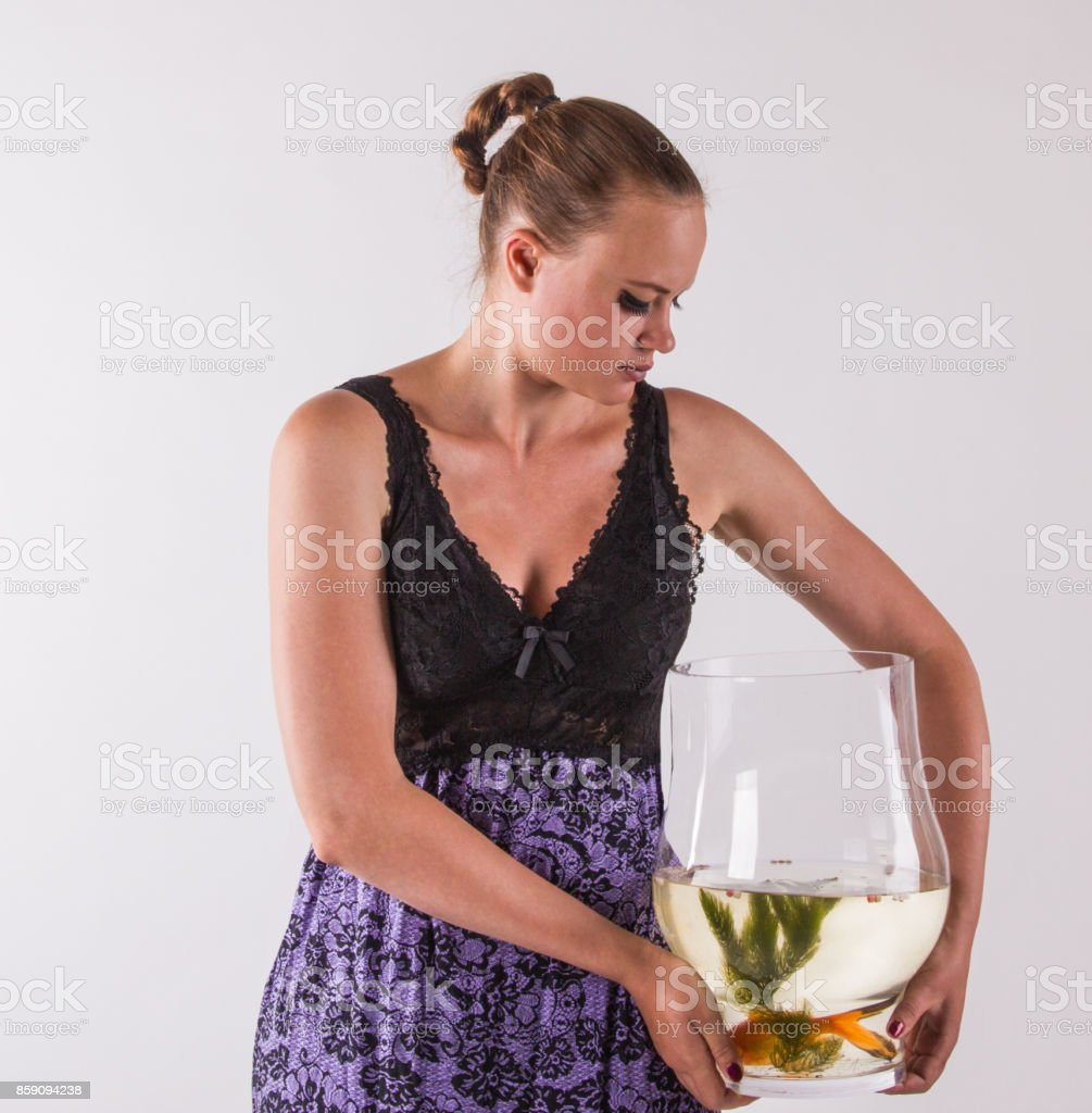 Attractive young woman, with aquarium with goldfish stock photo