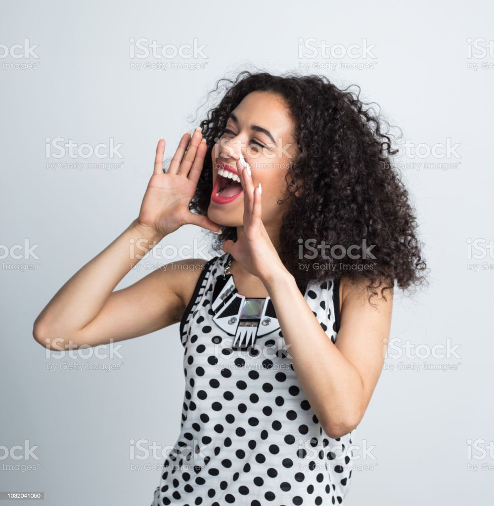 Attractive young woman with curly hair shouting away Attractive young woman with curly hair shouting away on white background 20-24 Years Stock Photo