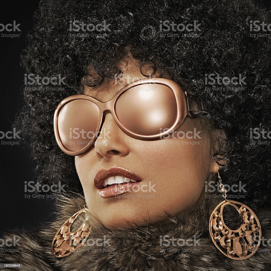 attractive young woman with curly hair wearing sunglasses royalty-free stock photo