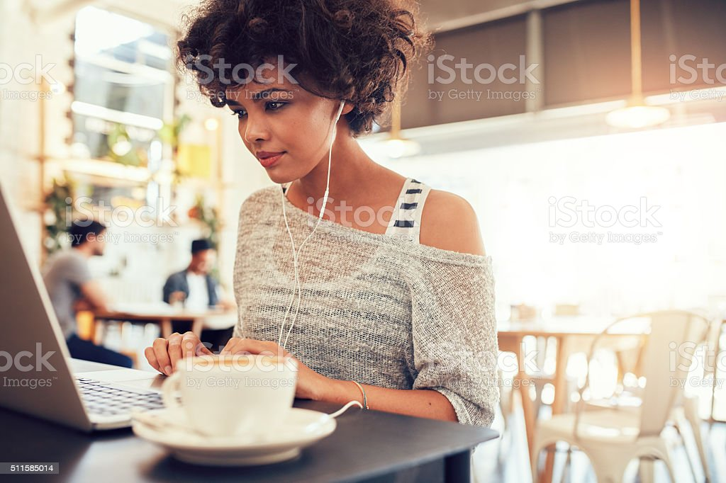 Attractive young woman with earphones using laptop at cafe stock photo