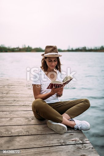 Attractive young woman with hat sitiing near water on wooden jetty.
