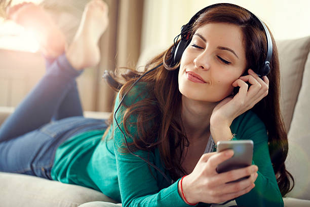 attractive young woman with headphones listens music on smart ph - free images for downloads stock photos and pictures