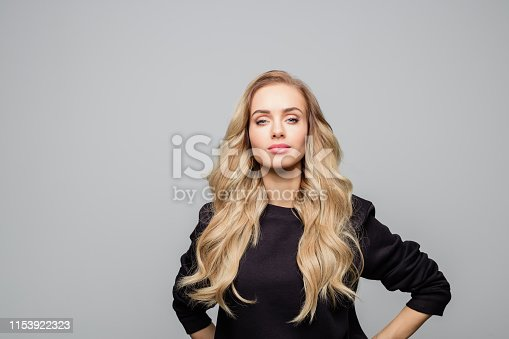 Portrait of attractive young woman with long blond hair. Urban female is with confident look on her face. She is wearing black top against white background.
