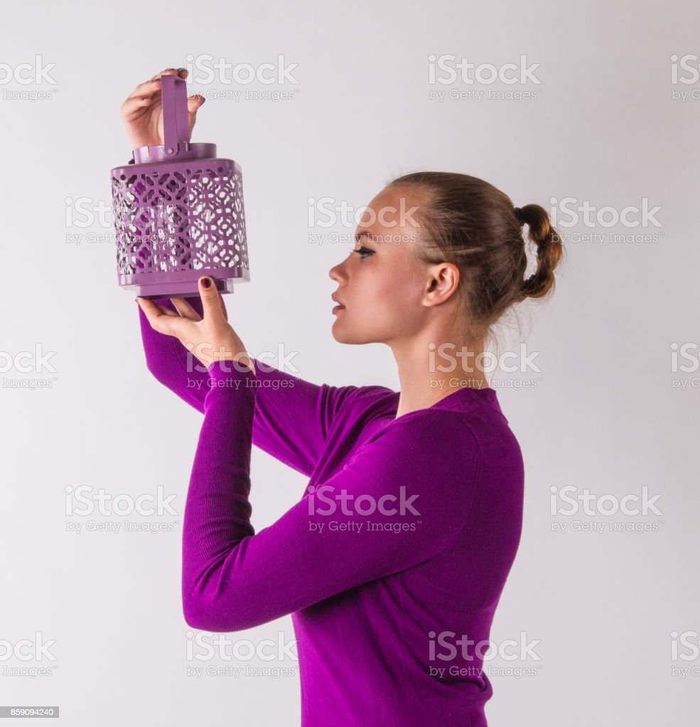 Attractive young woman, with magenta dress looks concern in a candlestick stock photo
