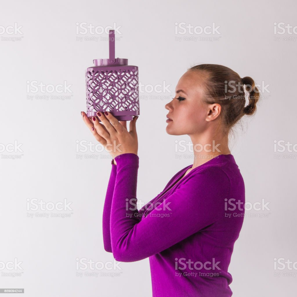 Attractive young woman, with magenta dress looks serenity in candlestick stock photo