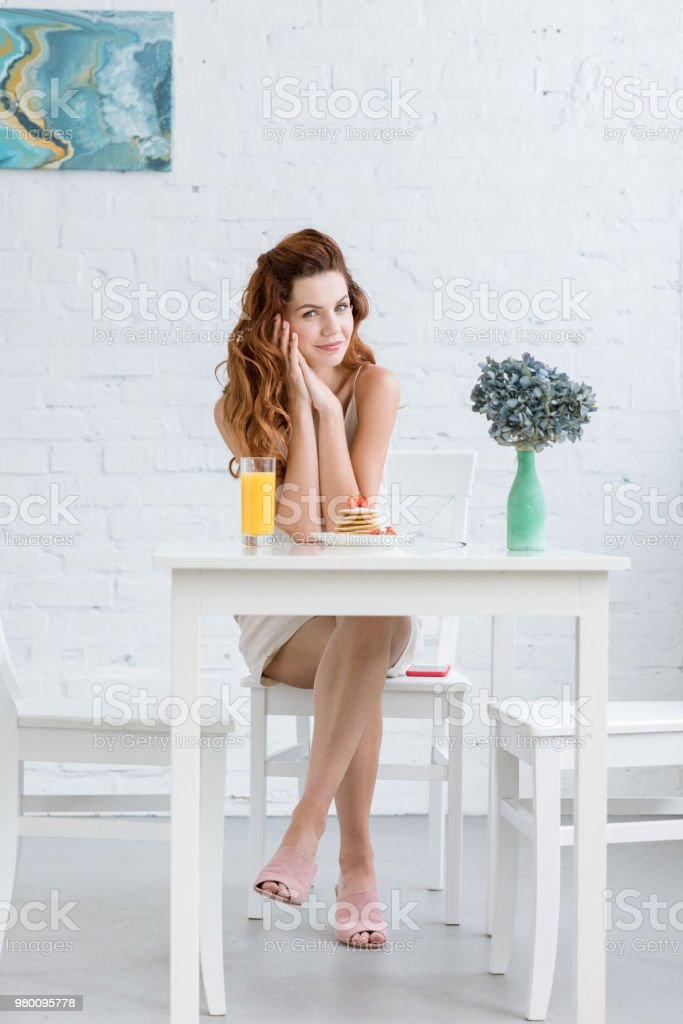 attractive young woman with orange juice and pancakes with strawberry for breakfast at home stock photo