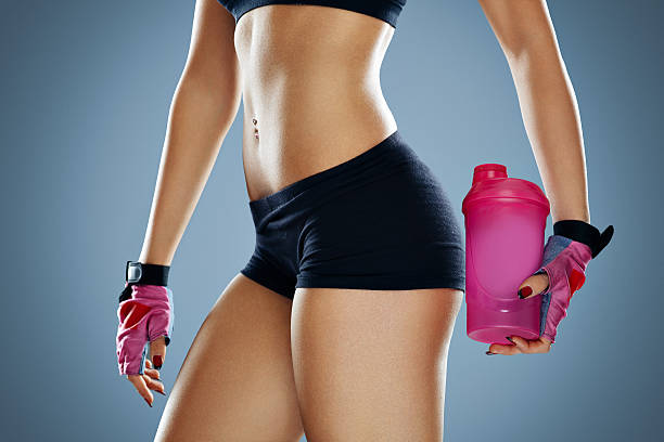 attractive young woman with protein shake bottle - body parts of sexy girls stock pictures, royalty-free photos & images