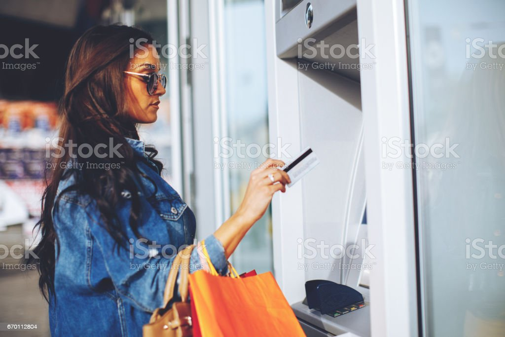 Attractive young woman withdrawing money from credit card at ATM stock photo