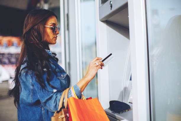 Attractive young woman withdrawing money from credit card at ATM - foto de stock