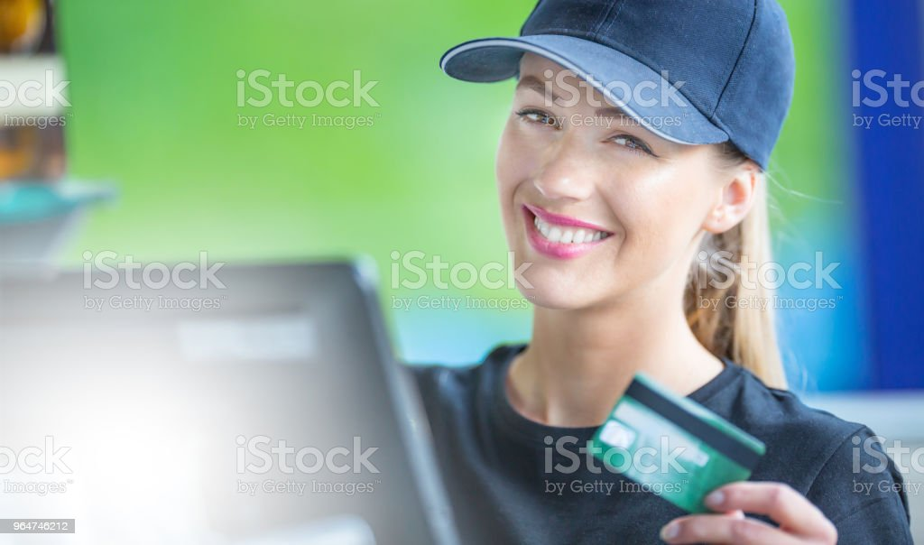 Attractive young woman working at a cash desk with a credit card royalty-free stock photo