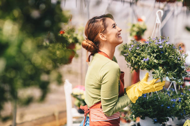 Attractive young woman working in a garden center. stock photo