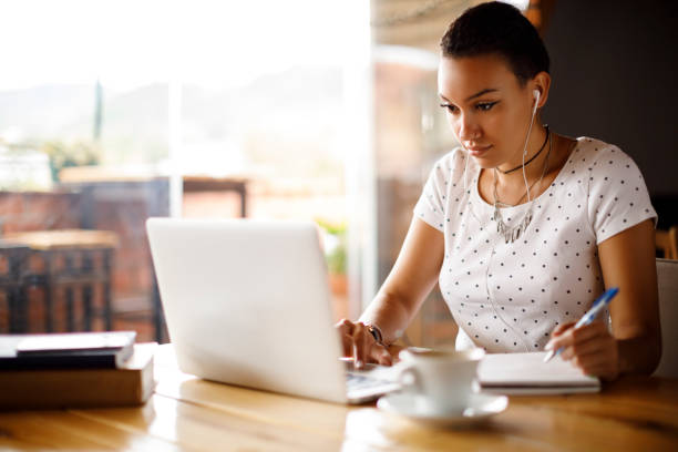 Attractive young woman working on laptop and taking notes at a cafe stock photo