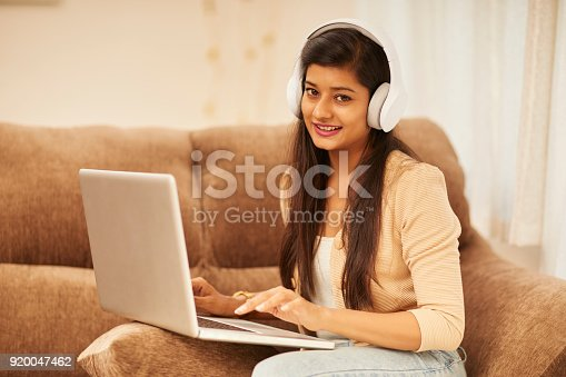 637756964 istock photo Attractive young woman working on laptop with headphones 920047462