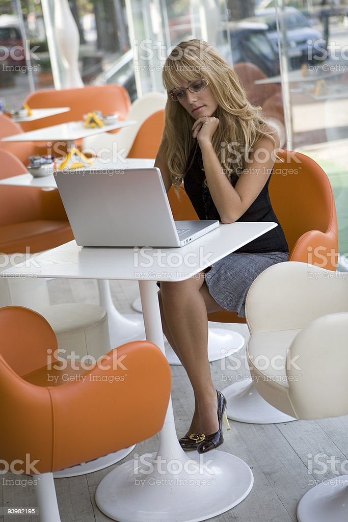 Attractive young woman working with laptop computer in a cafe royalty-free stock photo