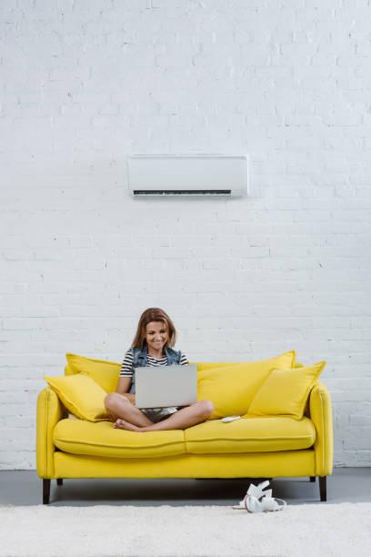 attraktiv ung kvinna som arbetar med laptop medan du sitter på soffan under luftkonditioneringen hängande på väggen - kvinna ventilationssystem bildbanksfoton och bilder